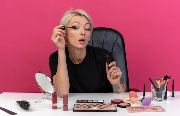 La giovane bella ragazza piacevole si siede alla tavola con gli strumenti di trucco che applicano il mascara isolato sulla parete rosa