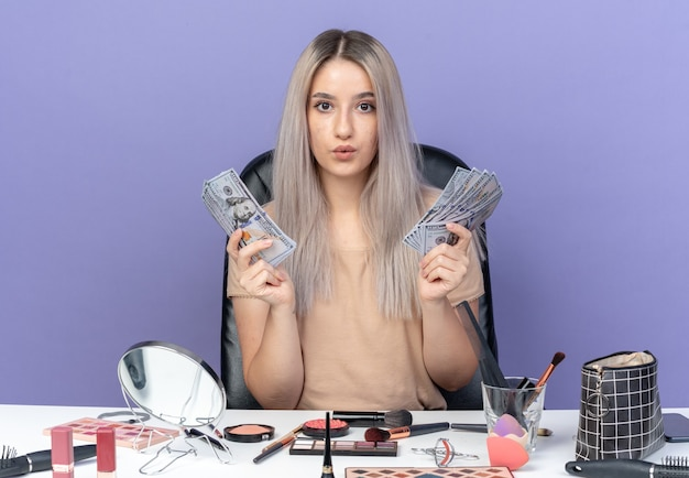 Pleased young beautiful girl sits at table with makeup tools holding cash isolated on blue wall