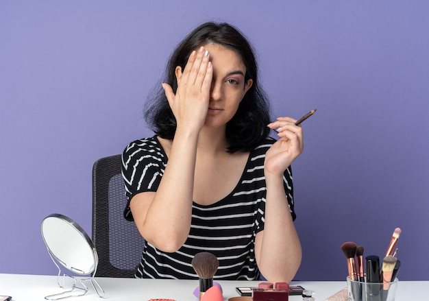 La giovane bella ragazza piacevole si siede alla tavola con gli strumenti di trucco che tengono l'occhio coperto di eyeliner con la mano isolata sulla parete blu