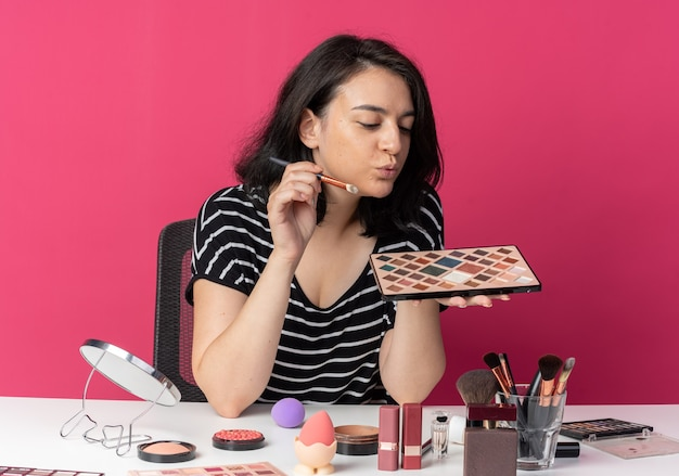 Pleased young beautiful girl sits at table with makeup tools holding and looking at eyeshadow palette with makeup brush isolated on pink wall