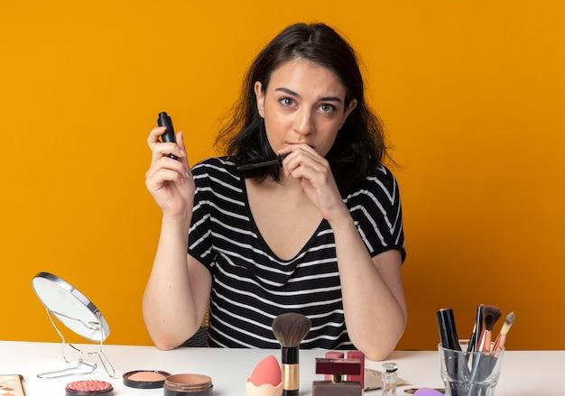 La giovane bella ragazza piacevole si siede alla tavola con gli strumenti di trucco che tengono il mascara isolato sulla parete arancione