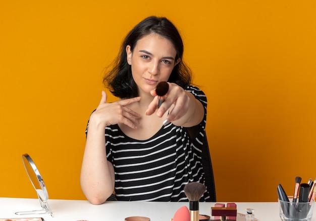 La giovane e bella ragazza contenta si siede al tavolo con gli strumenti per il trucco tenendo fuori il pennello per la polvere isolato sul muro arancione orange