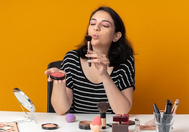 La giovane e bella ragazza contenta si siede al tavolo con gli strumenti per il trucco tenendo il fard in polvere e soffiando il pennello in mano isolata sul muro arancione