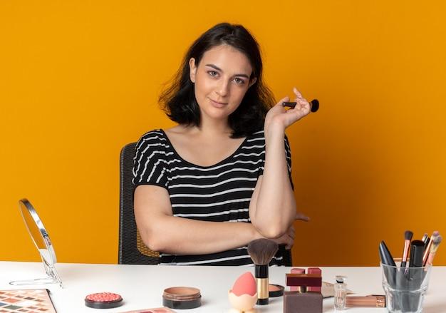 La giovane bella ragazza piacevole si siede alla tavola con gli strumenti di trucco che tengono la spazzola della polvere isolata sulla parete arancio