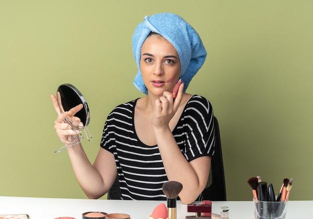 La giovane bella ragazza piacevole si siede al tavolo con gli strumenti di trucco i capelli avvolti in un asciugamano che tiene il rossetto con lo specchio