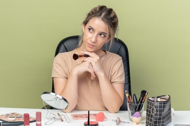 Довольная молодая красивая девушка сидит за столом с инструментами для макияжа, держа кисть для макияжа, изолированную на оливково-зеленой стене