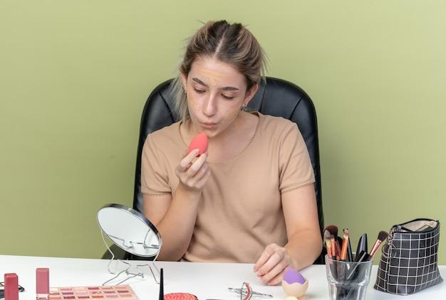 オリーブグリーンの壁に分離されたスポンジでトーンアップクリームを拭く化粧ツールで机に座って喜んで若い美しい少女