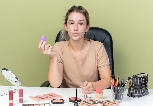 オリーブグリーンの壁に分離されたスポンジを保持している顔にトーンアップクリームと化粧ツールで机に座って喜んで若い美しい少女