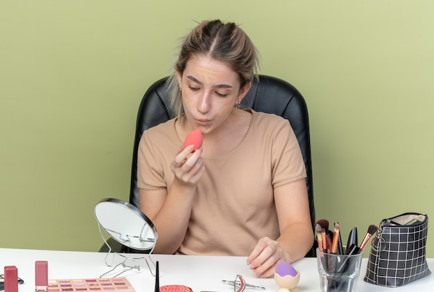 Lieta giovane bella ragazza seduta alla scrivania con strumenti per il trucco che pulisce la crema tonificante con una spugna isolata sul muro verde oliva