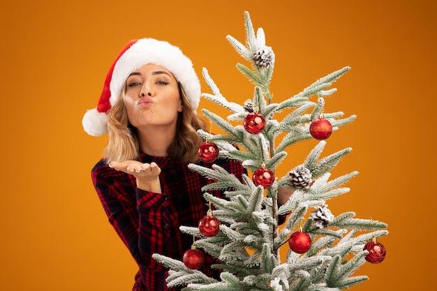 オレンジ色の背景に分離されたキスジェスチャーを示すクリスマス帽子をかぶってクリスマスツリーの後ろに立って喜んで若い美しい少女