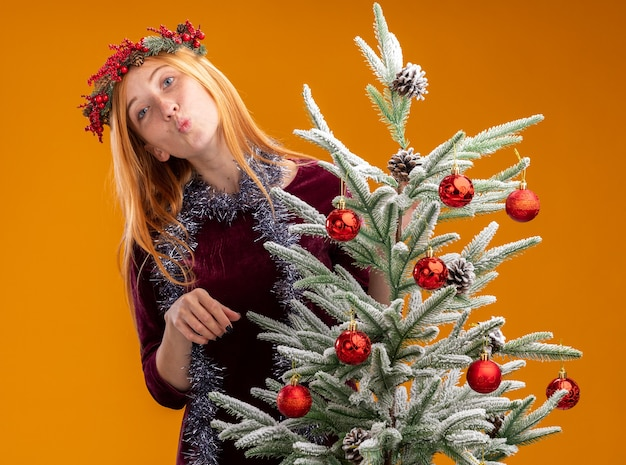 Pleased young beautiful girl standing behind christmas tree wearing red dress and wreath with garland on neck showing kiss gesture isolated on orange wall