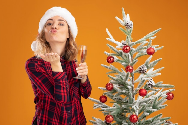 Pleased young beautiful girl standing nearby christmas tree wearing christmas hat holding glass of champagne showing kiss gesture isolated on orange background