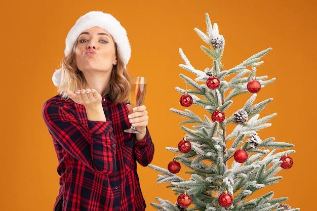 오렌지 배경에 고립 된 키스 제스처를 보여주는 샴페인 잔을 들고 크리스마스 모자를 쓰고 크리스마스 트리 근처에 서 기쁘게 젊은 아름 다운 소녀