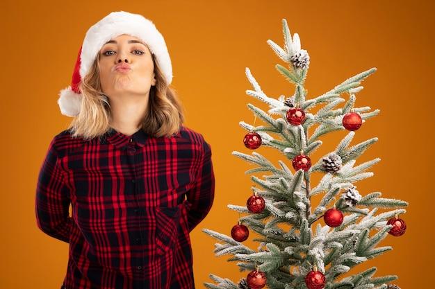 오렌지 배경에 고립 키스 제스처를 보여주는 크리스마스 모자를 쓰고 크리스마스 트리 근처에 서 기쁘게 젊은 아름 다운 소녀