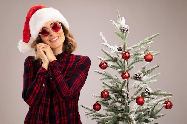 Lieta giovane bella ragazza in piedi vicino all'albero di natale che indossa il cappello di natale con gli occhiali isolato sul muro bianco