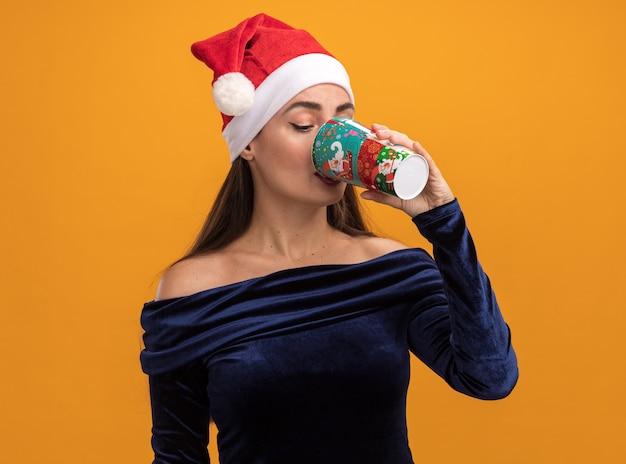Lieta giovane bella ragazza che indossa un abito blu e il cappello di natale beve dalla tazza di natale isolato su sfondo arancione