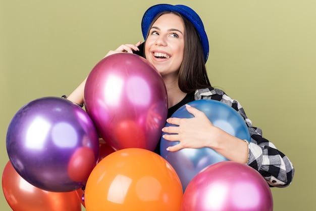 풍선 뒤에 서 있는 파란색 모자를 쓴 아름다운 소녀가 전화 통화를 하는 것을 기쁘게 생각합니다.