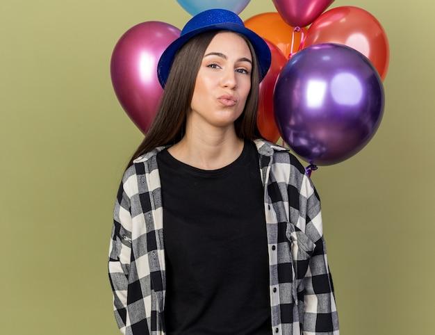 Довольная молодая красивая девушка в синей шляпе, стоящая перед воздушными шарами