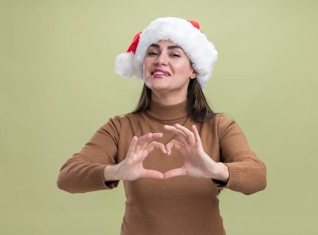 オリーブグリーンの背景で隔離の心のジェスチャーを示すクリスマス帽子をかぶって喜んで若い美しい少女