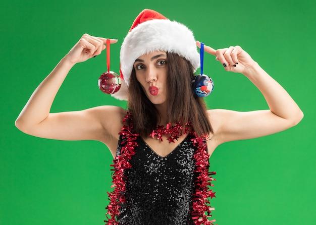 Довольная молодая красивая девушка в новогодней шапке с гирляндой на шее, держащая елочные шары, показывая жест поцелуя, изолированный на зеленой стене