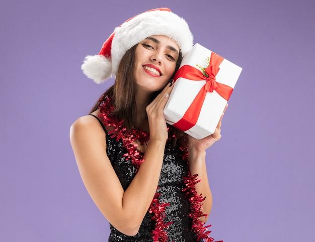 보라색 배경에 고립 된 얼굴 주위에 선물 상자를 들고 목에 갈 랜드와 함께 크리스마스 모자를 쓰고 기쁘게 젊은 아름 다운 소녀