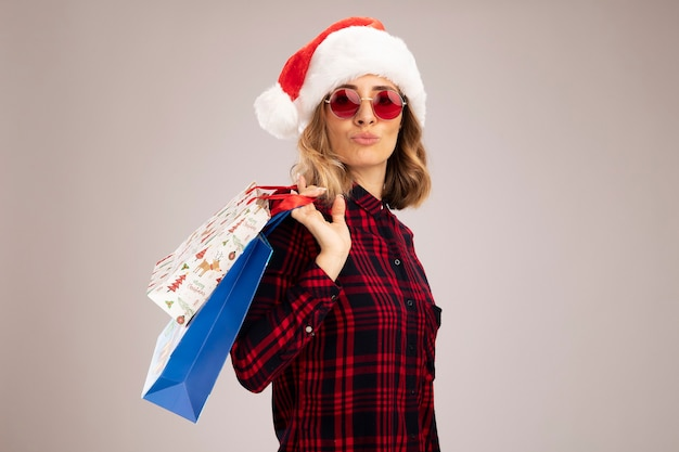 Pleased young beautiful girl wearing christmas hat with glasses holding gift bag on shoulder isolated on white background