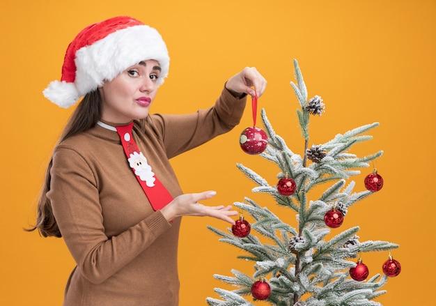 Довольная молодая красивая девушка в новогодней шапке с галстуком стоит рядом с елкой с елочным шаром на оранжевом фоне