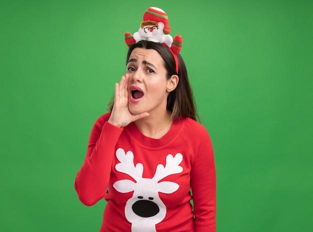 Довольная молодая красивая девушка в рождественском свитере с рождественским обручем для волос зовет кого-то изолированного на зеленом фоне