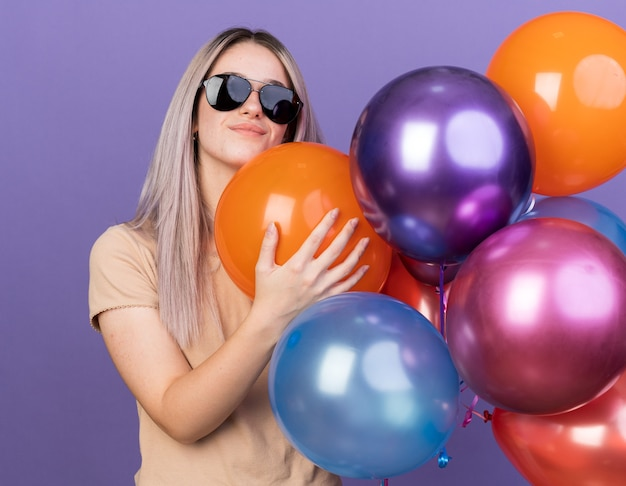 Pleased young beautiful girl wearing glasses holding balloons isolated on blue wall