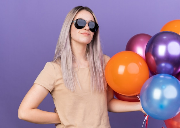 Pleased young beautiful girl wearing glasses holding balloons putting hand on hip