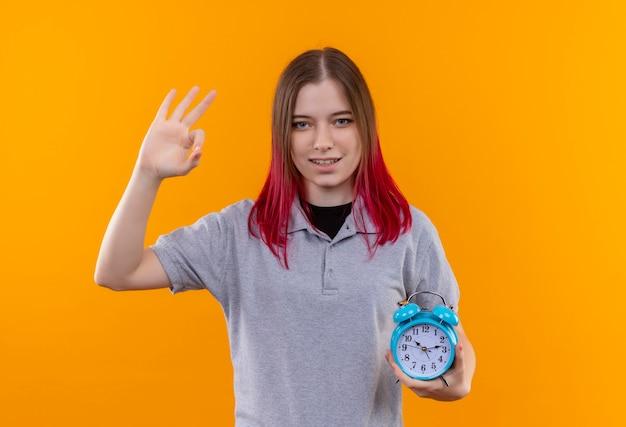 孤立した黄色の背景に大丈夫なジェスチャーを示す目覚まし時計を保持している灰色のtシャツを着て喜んで若い美しい少女