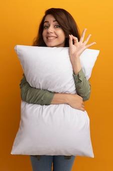 La giovane bella ragazza soddisfatta che indossa la maglietta verde oliva ha abbracciato il cuscino che mostra il gesto giusto isolato sulla parete gialla