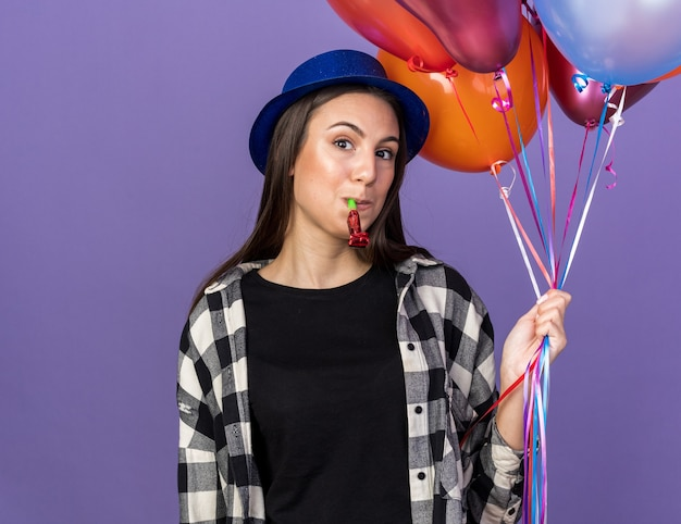 Pleased young beautiful girl wearing party hat holding balloons blowing party whistle