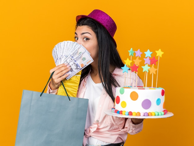 Pleased young beautiful girl wearing party hat holding cake with gift bag and covered face with cash isolated on orange wall