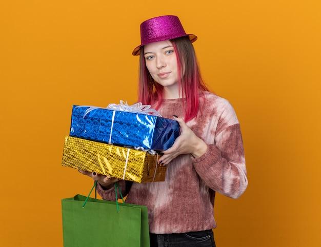 Довольная молодая красивая девушка в шляпе партии держит подарочный пакет с подарочными коробками, изолированными на оранжевой стене