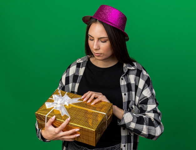 Pleased young beautiful girl wearing party hat holding and looking at gift box isolated on green wall