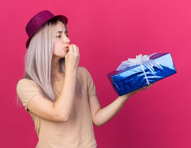 Felice giovane bella ragazza che indossa un cappello da festa che tiene e guarda una confezione regalo che mostra un gesto delizioso isolato su una parete rosa
