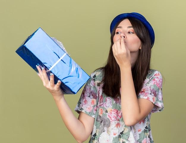 Felice giovane bella ragazza che indossa un cappello da festa che tiene in mano e guarda la confezione regalo che mostra un gesto delizioso