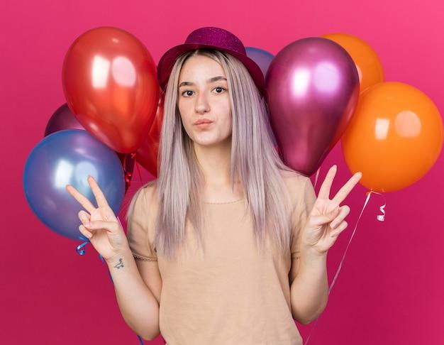 平和のジェスチャーを示す前の風船に立っているパーティーハットを身に着けている若い美しい少女を喜ばせる
