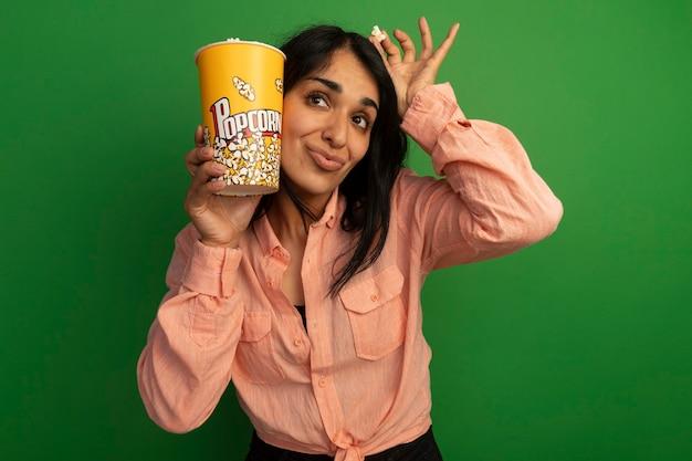 Довольная молодая красивая девушка в розовой футболке держит ведро попкорна с миром попкорна вокруг лица, изолированного на зеленой стене