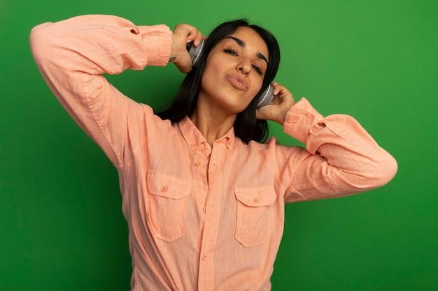 Довольная молодая красивая девушка в розовой футболке с наушниками изолирована на зеленой стене