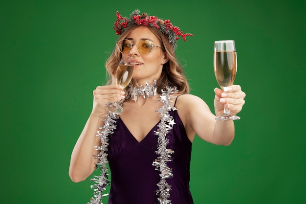 Довольная молодая красивая девушка в фиолетовом платье и стекле и венке с гирляндой на шее, протягивая бокал шампанского перед камерой, изолированной на зеленом фоне