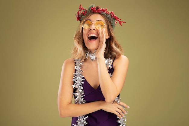 Довольная молодая красивая девушка в фиолетовом платье и очках с венком и гирляндой на шее зовет кого-то изолированного на оливково-зеленой стене