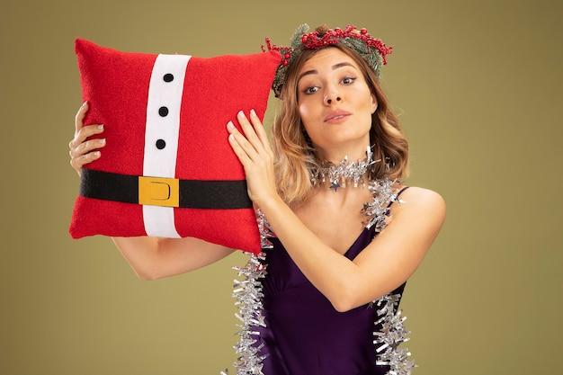 올리브 녹색 배경에 고립 된 크리스마스 베개를 들고 목에 갈 랜드와 보라색 드레스와 화 환을 입고 기쁘게 젊은 아름 다운 소녀