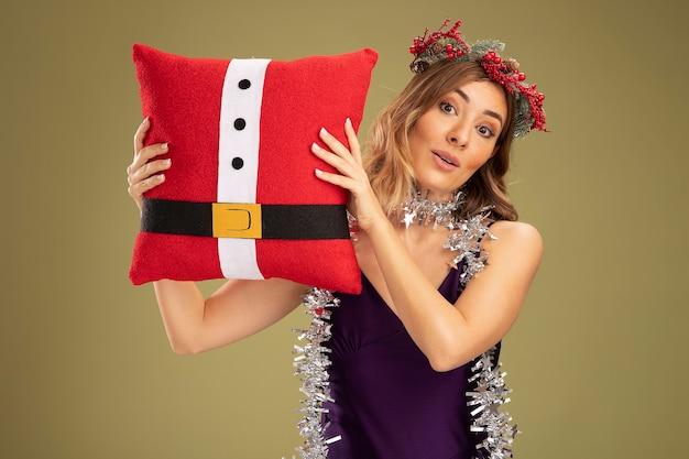 オリーブグリーンの背景で隔離のクリスマス枕を保持している首に花輪と紫色のドレスと花輪を身に着けている若い美しい少女