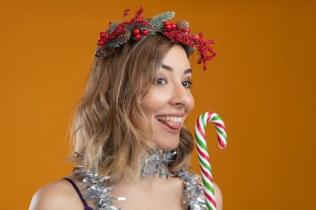 茶色の背景で隔離のクリスマスキャンディーを保持している首に花輪と花輪と紫色のドレスを着て喜んで若い美しい少女