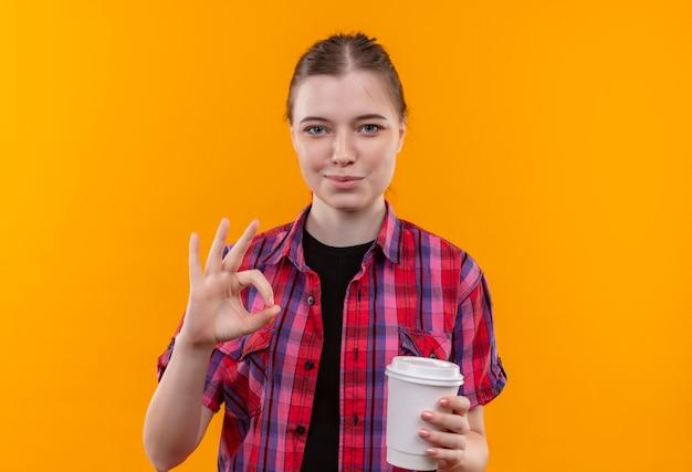 Довольная молодая красивая девушка в красной рубашке, держащая чашку кофе, показывая жест окей на изолированном желтом фоне с копией пространства