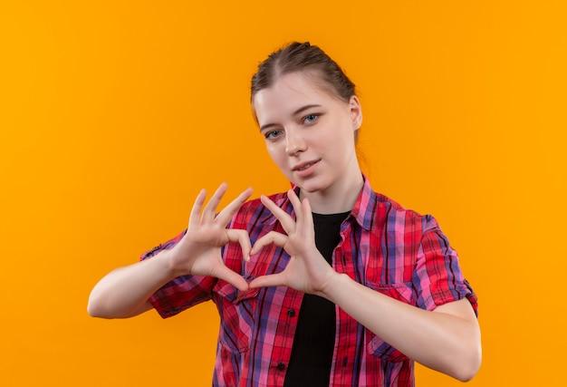 Lieta giovane bella ragazza che indossa la camicia rossa che mostra il gesto del cuore su sfondo giallo isolato