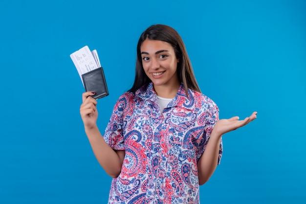 Довольная молодая красивая женщина-путешественница, стоящая с билетами и паспортом, выглядит уверенно улыбаясь, представляя руку, стоящую на синем фоне
