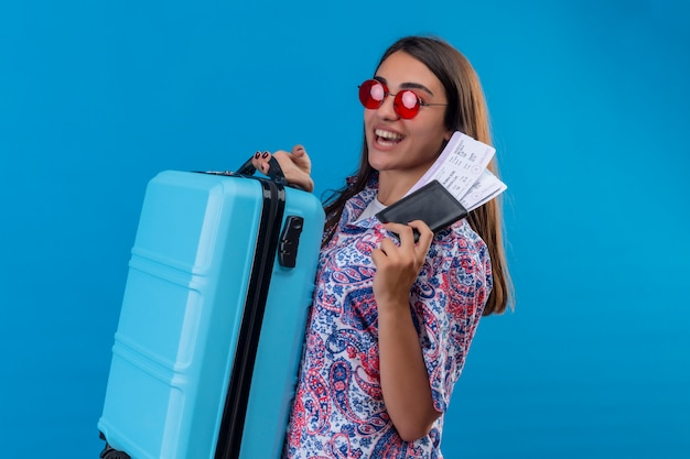 Pleased young beautiful traveler woman wearing red sunglasses holding blue suitcase and tickets smiling cheerfully with happy face over blue wall